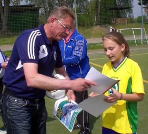 Herr Grahl (Landesfußballverband M/V) übergibt die Unterlagen an Emely Sponholz (5b)